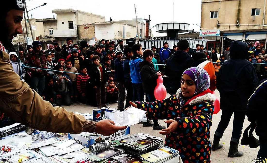 En IS-man delar ut läsk, godis och religiösa pamfletter till barn i samband med en stadspredikan i Raqqa-provinsen i Syrien.