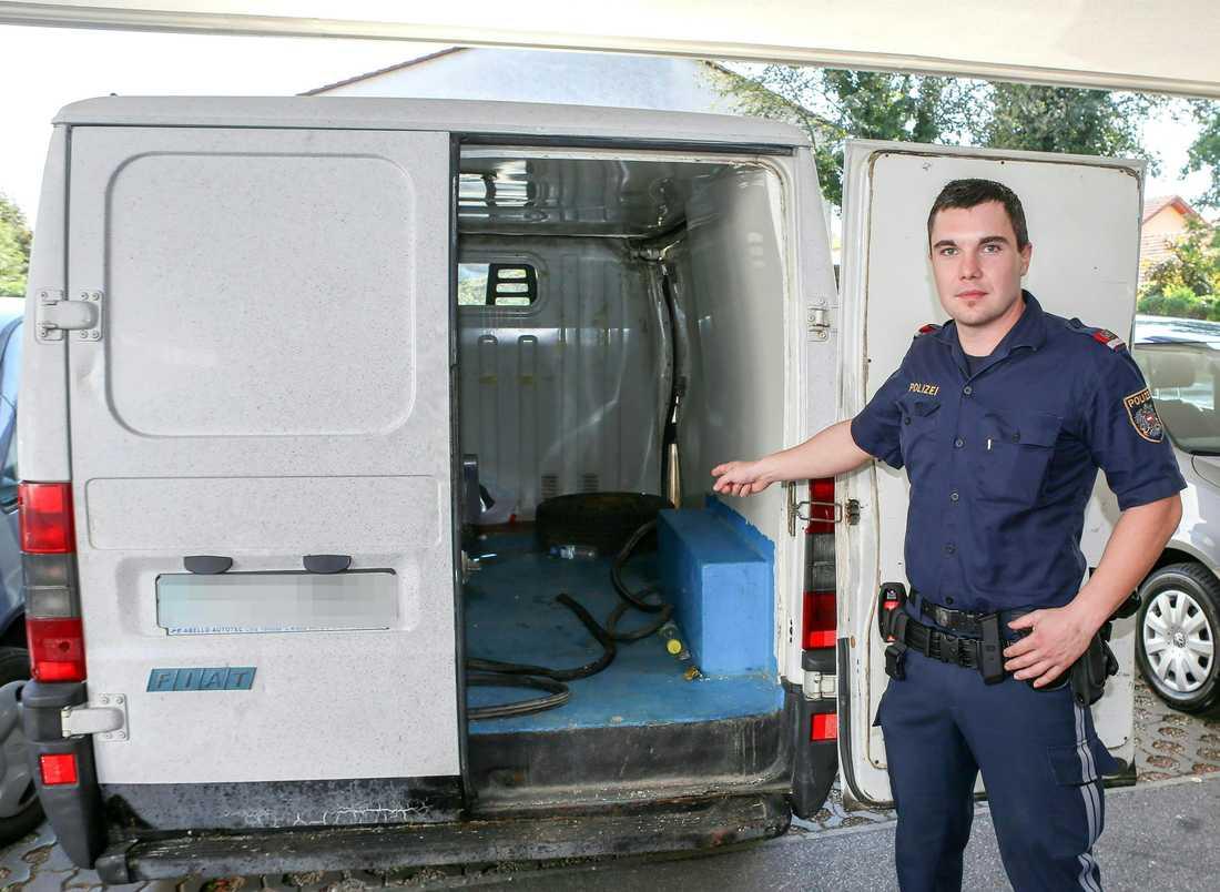 En polis i Österrike visar upp skåpbilen där 26 flyktingar hittades instängda.