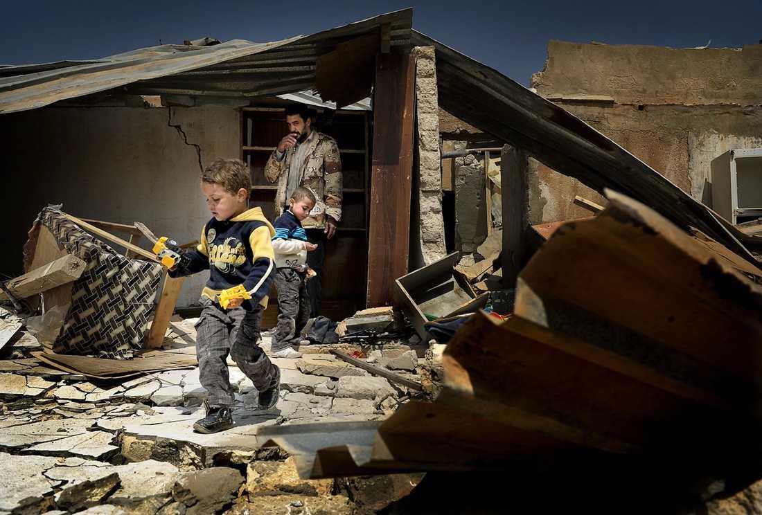 """BARA RUINER KVAR Adel Rahid har återvänt till sitt sönderbombade hem med sina två brorsöner Alash, 4, och Adil, 6, sedan Gaddafis sista legosoldater flytt Ajdabiya. """"Vi är lättade och vi firar vår framtid"""", säger han."""