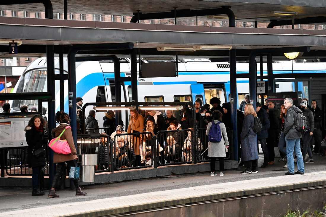 Personer utan munskydd trängs på en perrong i Stockholm.