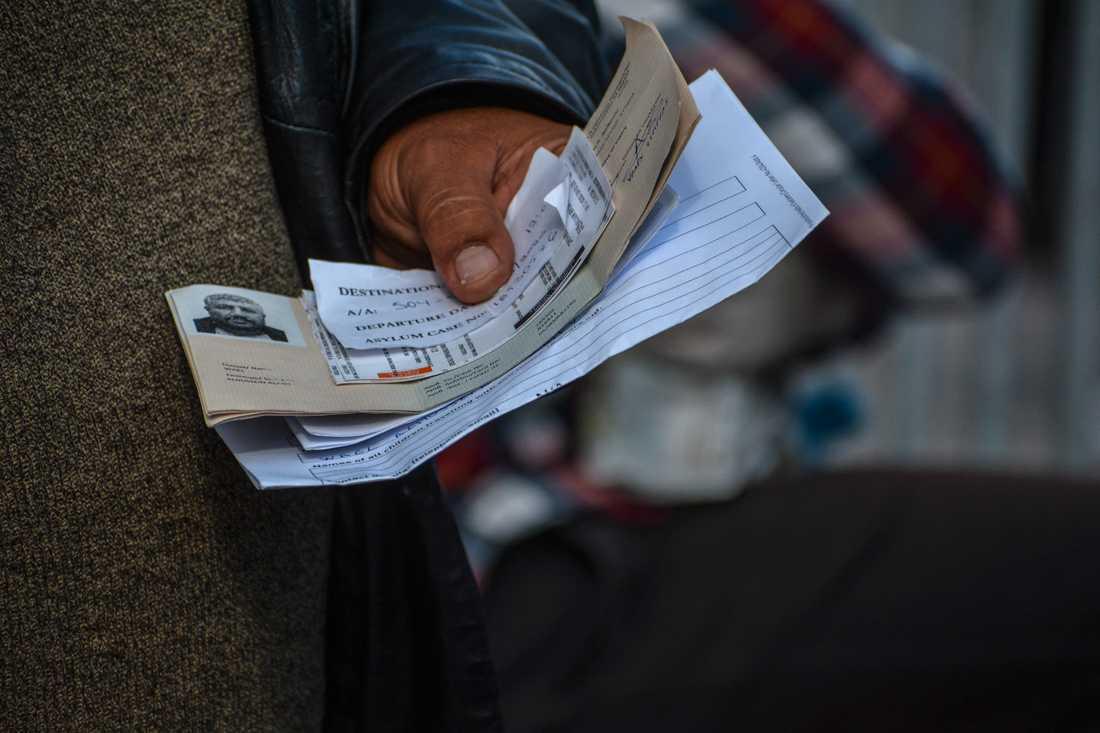 En man håller fram sina dokument för att få resa från ön Lesbos till hamnstaden Piraeus på fastlandet. Arkivbild.