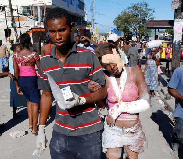 OMPLÅSTRAD En skadad kvinna har fått armen lindad och ansiktet omplåstrat efter att ha räddats ur rasmassorna.