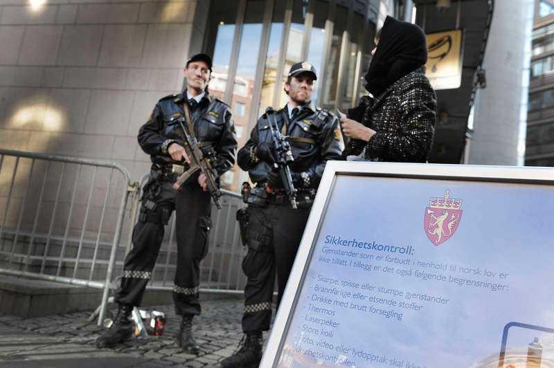 Tungt beväpnade poliser står utanför Oslo tingsrätt. Säkerheten vid rättegången är rigorös.