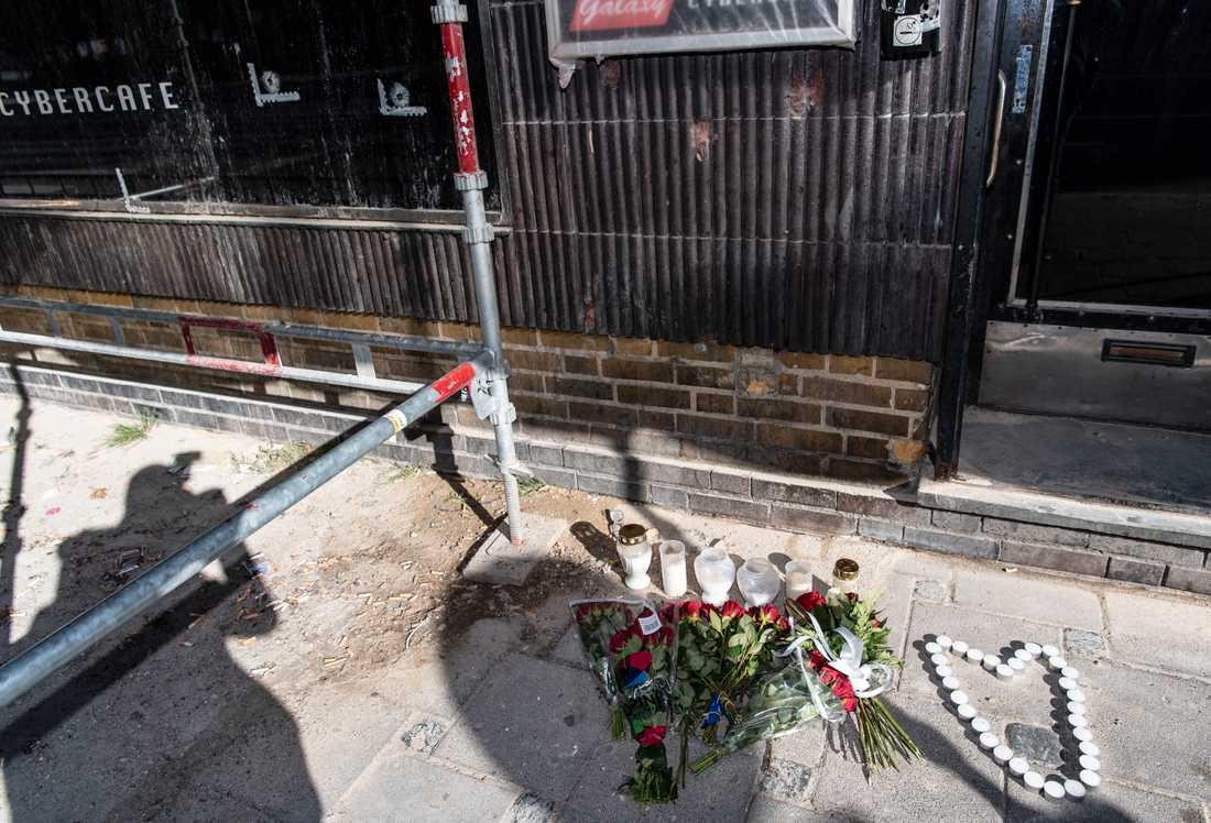 Blommor och ljus har placerats ut där tre gängkriminella män sköts ihjäl och tre andra skadades i måndags kväll.