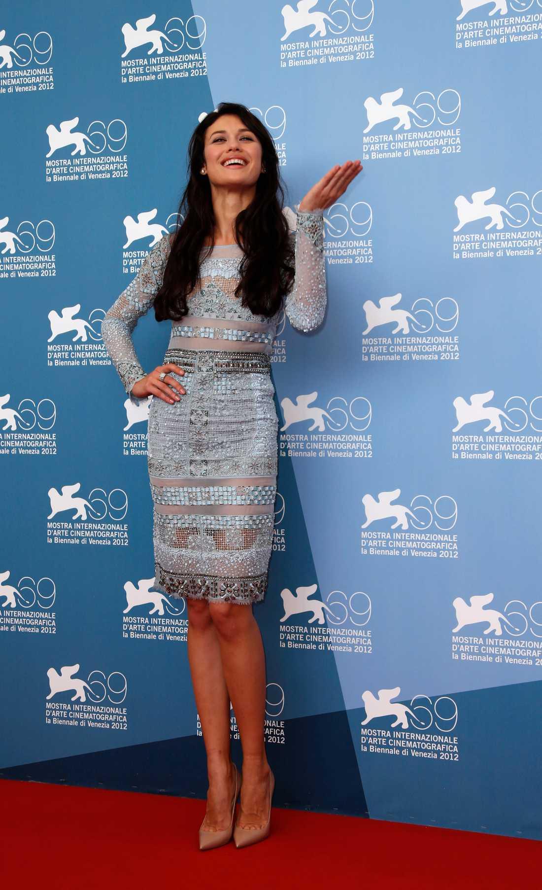 Olga Kurylenko, på filmfestival i Venedig 2012 Ännu en åtsittande klänning, som trots sina transparenta partier avslöjar lagom mycket tack vare de korta ärmarna. Denna ljusblå skapelse från Emilio Pucci kombineras ytterst stilfullt med begie pumps från Louboutin.