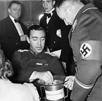 """Gustaf Adolf ger ett bidrag till nazistpartiets """"vinterhjälp till det tyska folket"""" under ett besök i Berlin 1939."""
