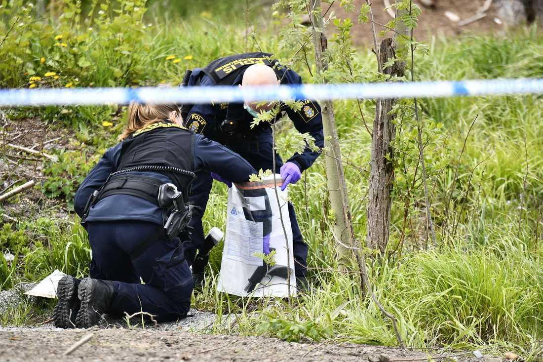Polisens tekniker undersöker ett vapen som hittats på platsen.