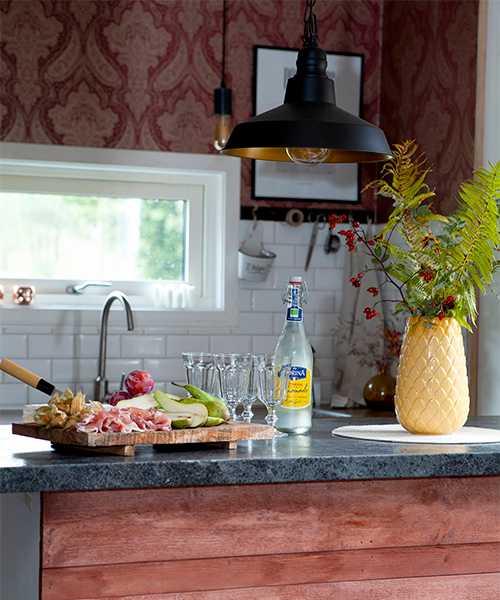 Köksön har fått sig en makeover med målade brädor. För att liva upp bordsytan har Kristin klistrat på dekorplast. Gul vas från H&M home. Tapet i bakgrunden från Rusta.