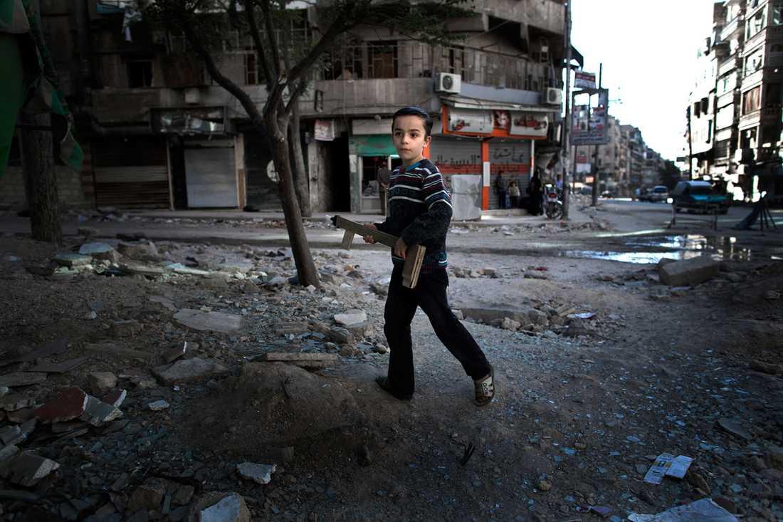 En ung pojke leker med ett hemmagjort leksaksgevär i Aleppo.