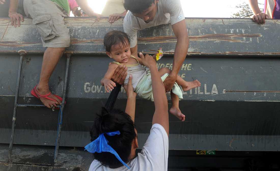 Ett litet barn tas om hand efter att Tacloban förstörts av tyfonen.