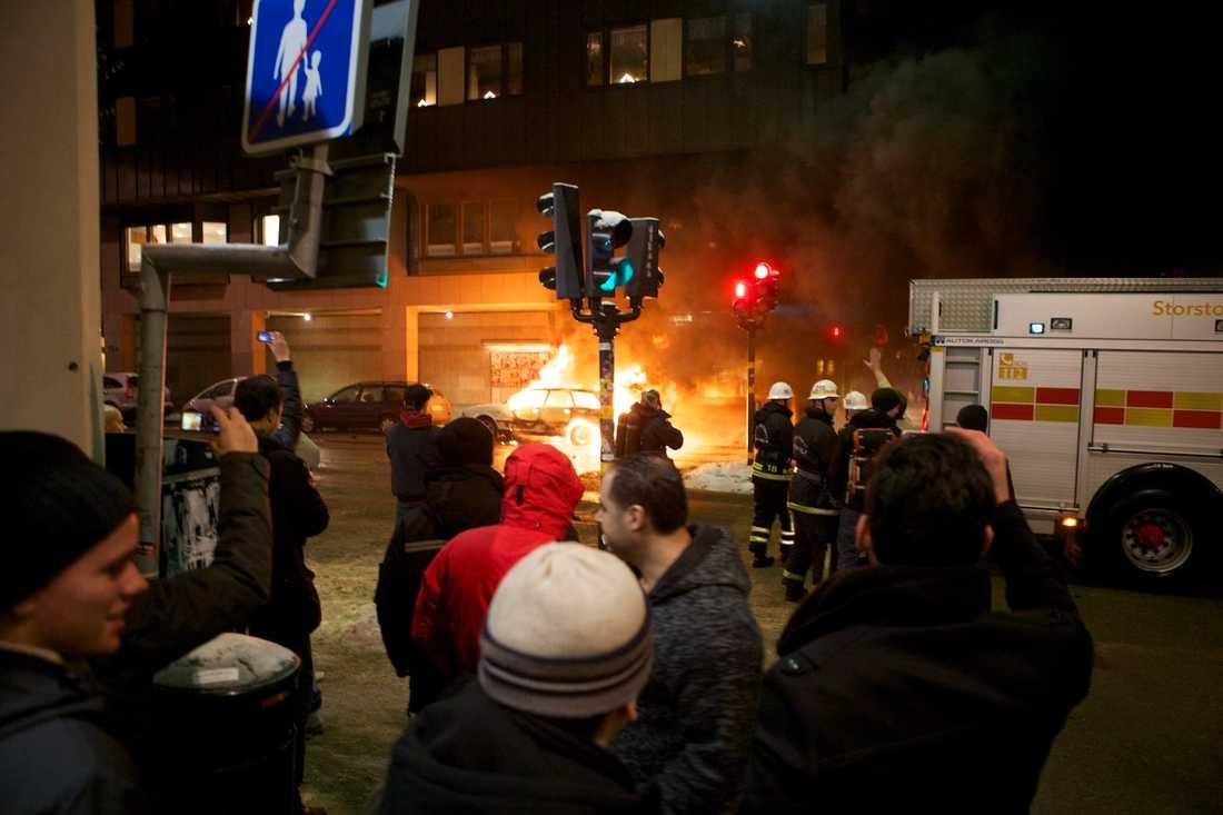 Folksamling Snabbt samlades en stor folksamling vid den brinnande bilen.