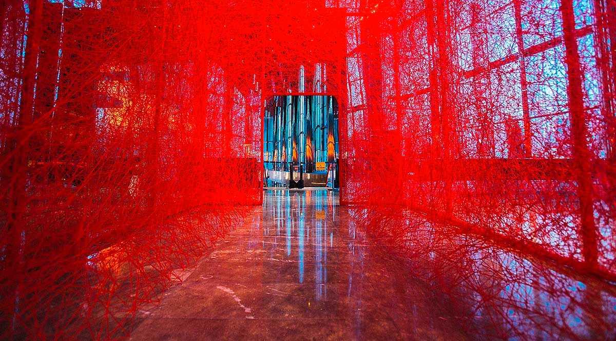 Chiharu Shiotas verk tecknar ett hus av rött garn i tre dimensioner.