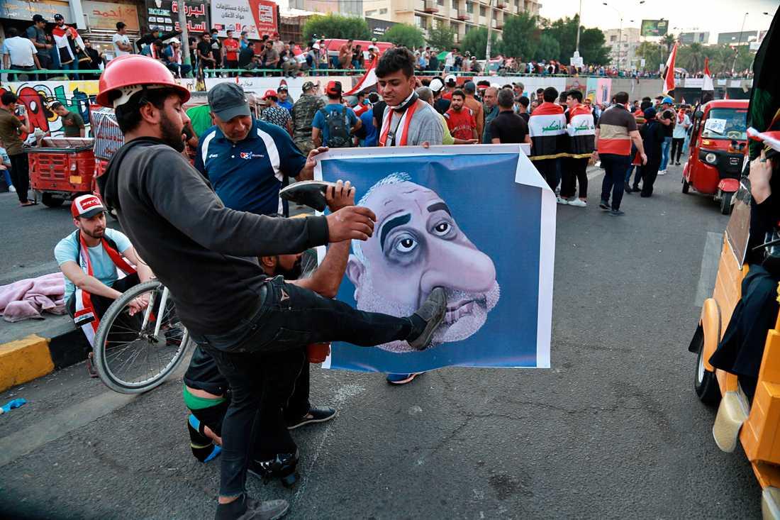 Irakiska demonstranter med ett nidporträtt av premiärminister Adil Abd al-Mahdi under förra helgens protester.