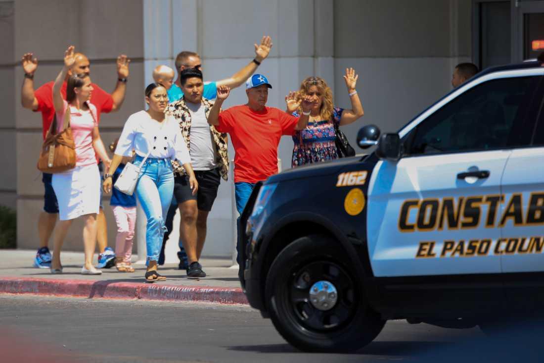 Med händerna i vädret lämnar folk shoppingcentret i El Paso, Texas, efter lördagens massaker.