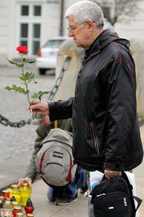 Sörjande lägger blommor vid presidentpalatset i Warzava.