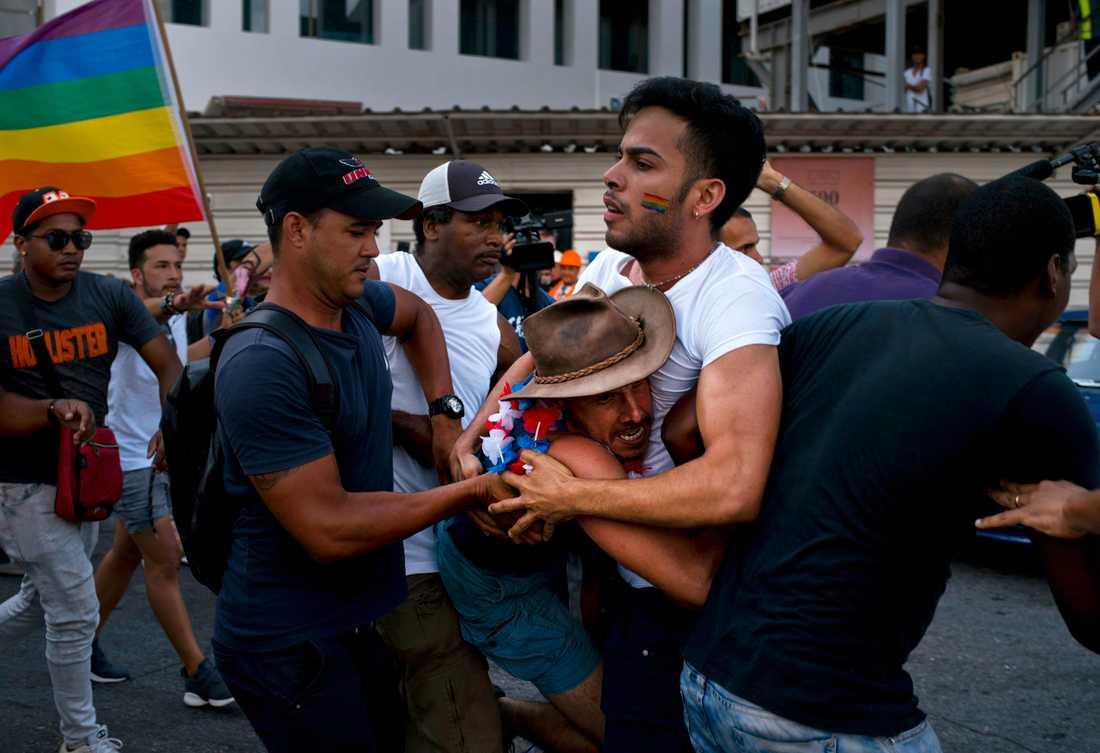 Civilklädd polis ingriper under en prideparad i Havanna, Kuba.