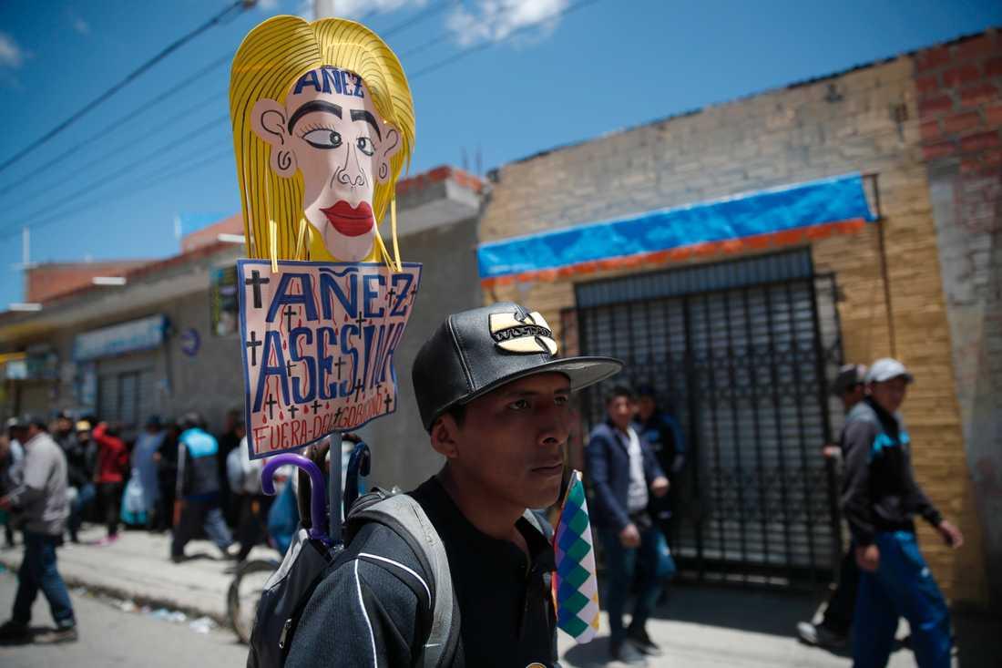 """En anhängare till den tidigare presidenten Evo Morales håller ett plakat med texten """"Jeanine Áñez lönnmördare, försvinn"""" under en demonstration i El Alto utanför huvudstaden La Paz."""