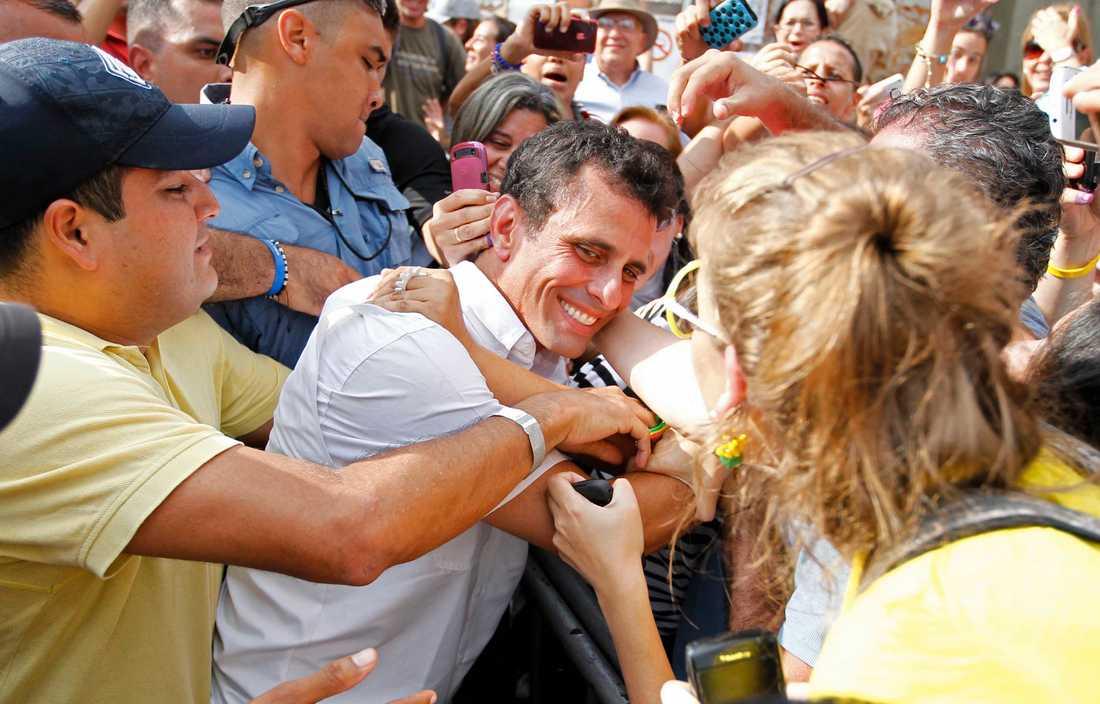 Anhängare av oppositionskandidaten Henrique Capriles hopas kring honom efter att han lämnat sin egen röst under söndagen. Enligt en första, inofficiell undersökning gick han ur valet som vinnare. Men Chávez vände och vann.