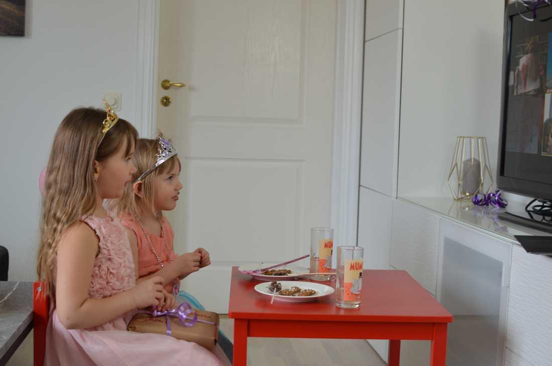 Sandra och hennes lillasyster Ellie fikar framför skärmen där kalasdeltagarna kopplat upp sig för att digitalt vara med på barnkalaset.