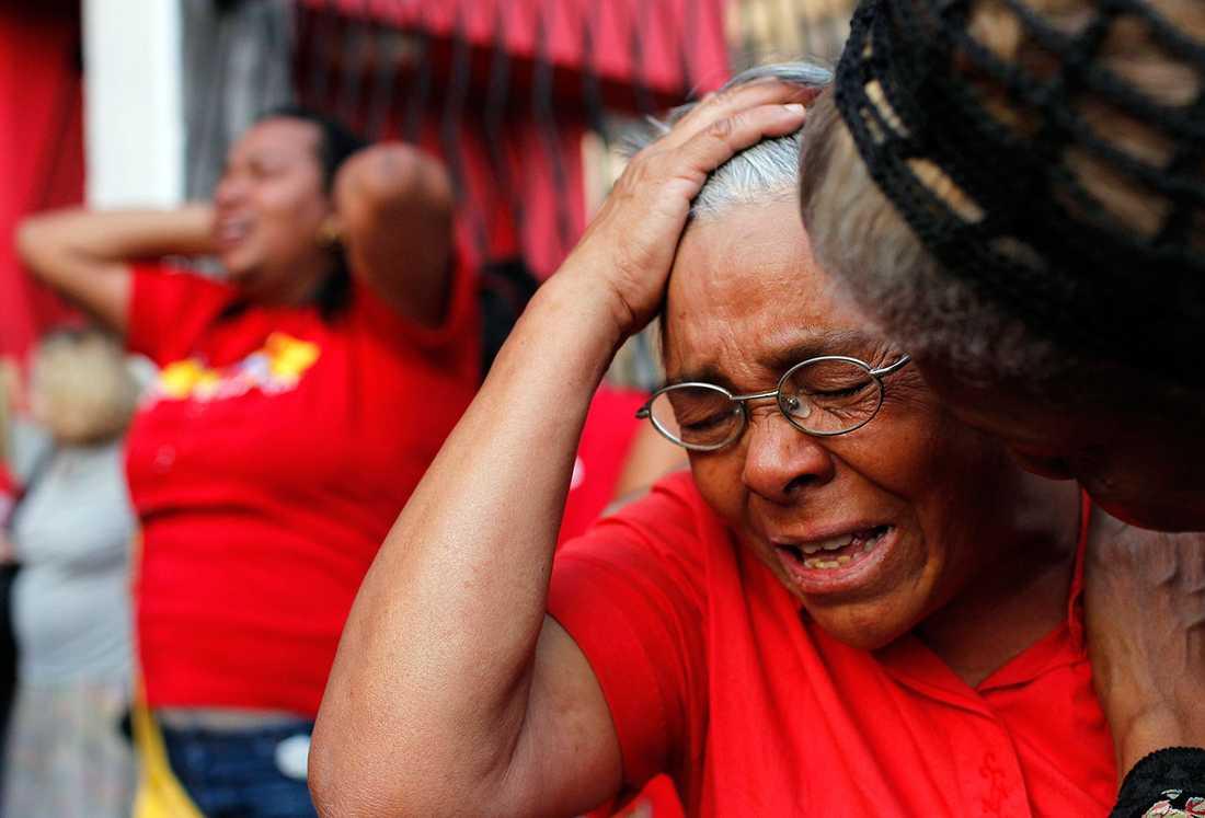 En kvinna i Caracas tröstas efter dödsbeskedet.