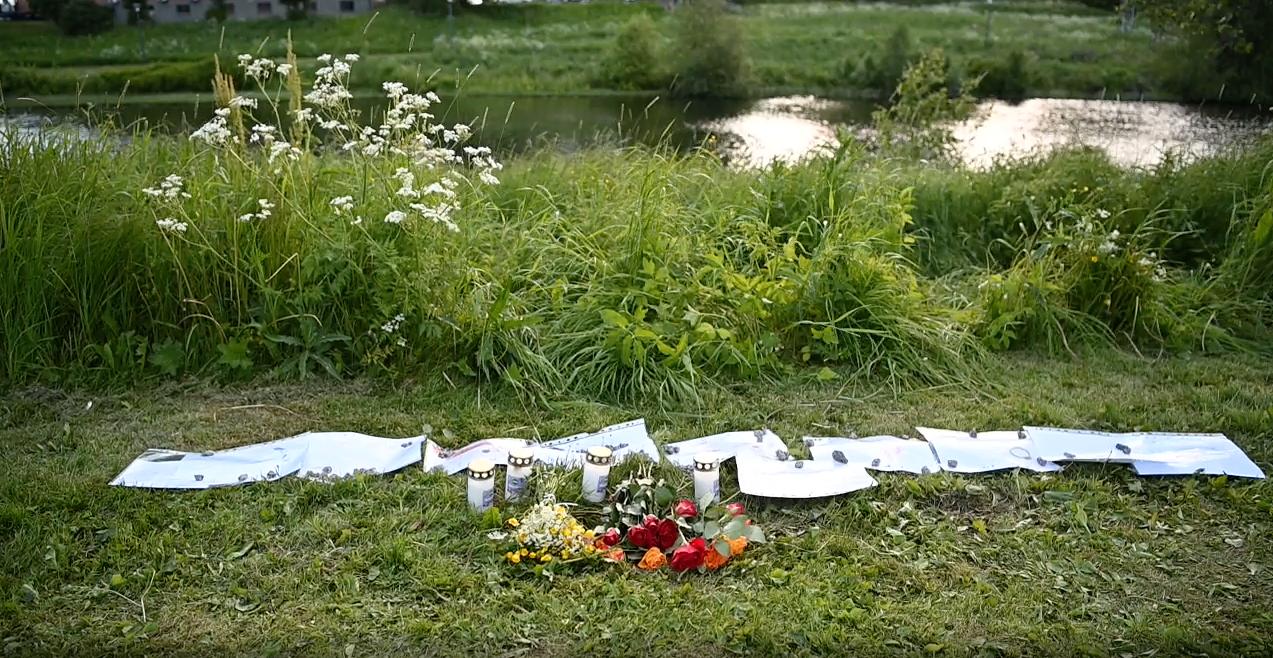Mitt i sommargrönskan råder plötsligt sorg i det värmländska samhället. Vid älven i centrala Hagfors har man lämnat blommor och ljus för att hedra den döde pojken.