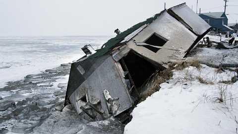 HAVET ÄTER UPP JORDEN Ett av husen i Shishmaref, Alaska, underminerades av stormvågorna och föll ner från strandkanten under en storm 2005. Snart måste hela byn flytta – innan samma sak händer även de andra husen. Allt som allt kommer flytten att kosta över en miljard svenska kronor för eskimåbefolkningen. Pengar de inte har.