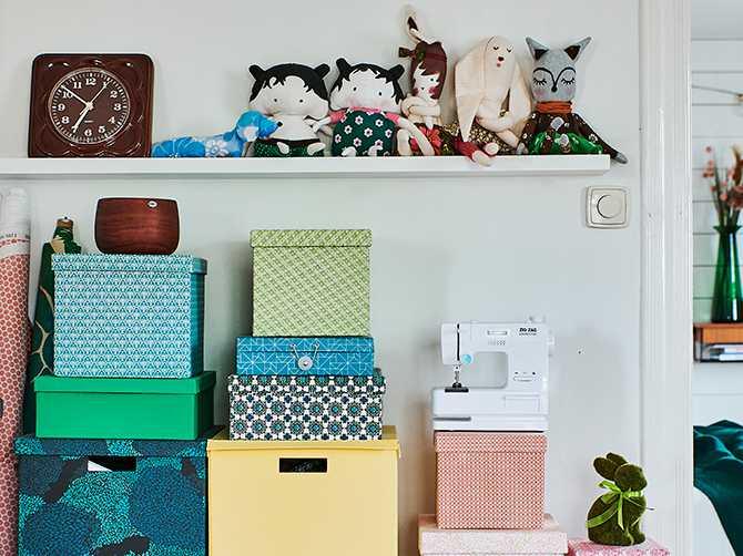 De färgglada boxarna rymmer pyssel och sytillbehör. På hyllan ovanför sitter egensydda dockor och gosedjur.