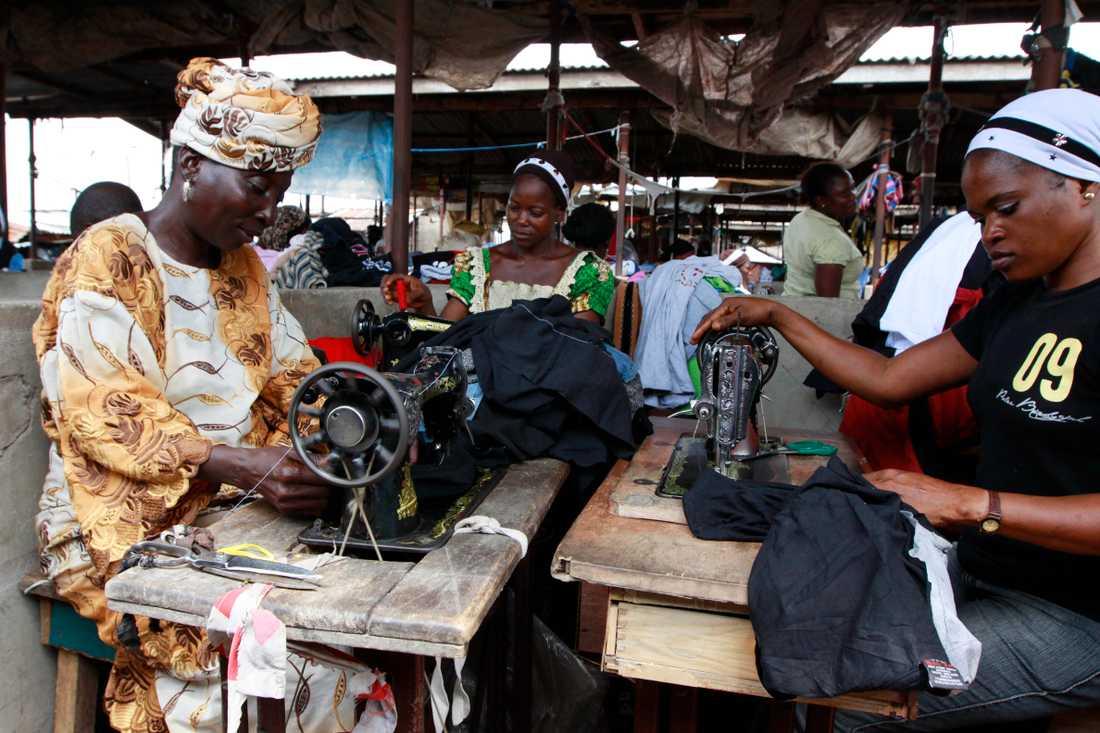 Kvinnor arbetar med lagning av kläder på en marknad i Lagos, Nigeria. Arkivbild.