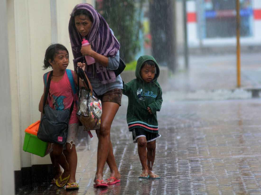 En mamma och hennes två barn flyr till ett evakueringscentrum i Cebu City.
