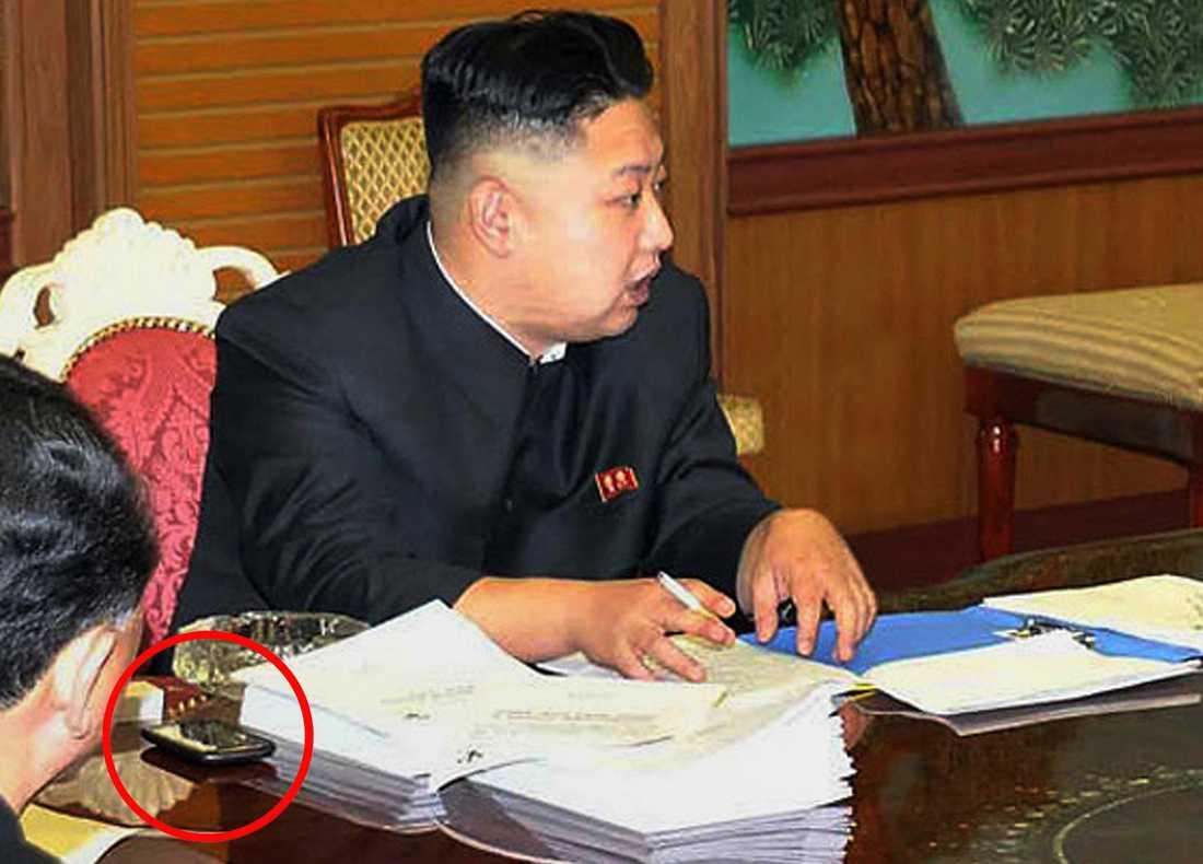 På bilden från Nordkoreas officiella nyhetsbyrå syns Kim Jong-Uns mystiska smartphone. Vad det är för en mobil har det än så länge bara spekulerats i.