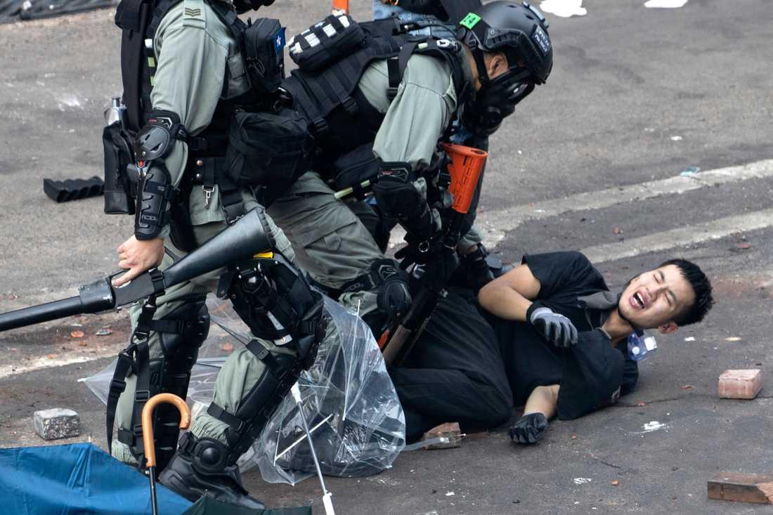 En ung man brottas ned av kravallpolis i anslutning till Hongkongs polytekniska universitet, där hundratals aktivister barrikaderade sig under måndagen.