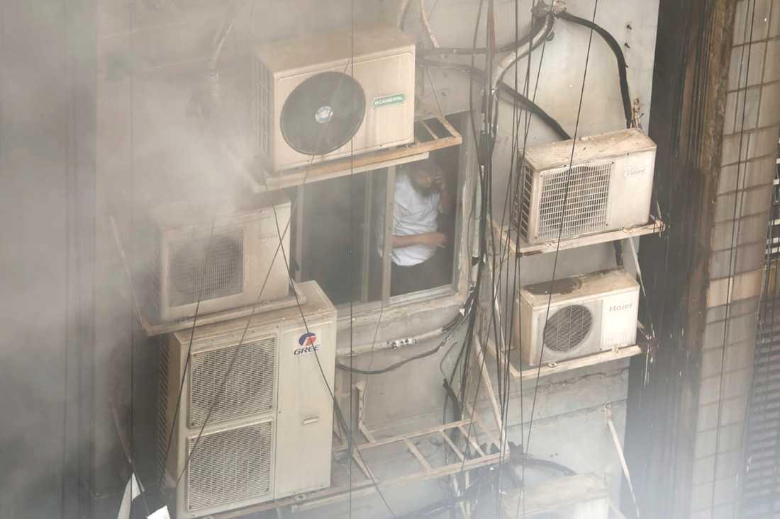 En man står  i den brinnande byggnaden.