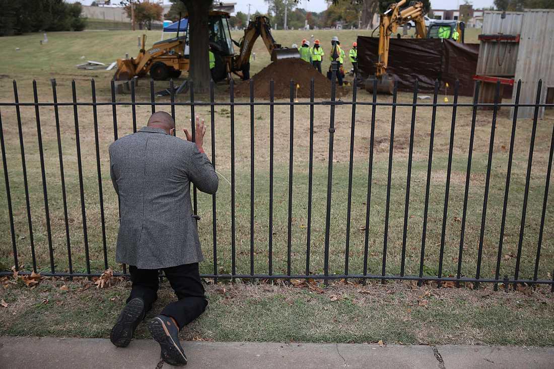Robert Turner, pastor vid kyrkan Vernon A.M.E. i Tulsa, knäböjer i bön vid Oaklawn Cemetery medan arkeologer letar efter kvarlevor efter offren för massakern 1921. Bilden är från den 20 oktober.
