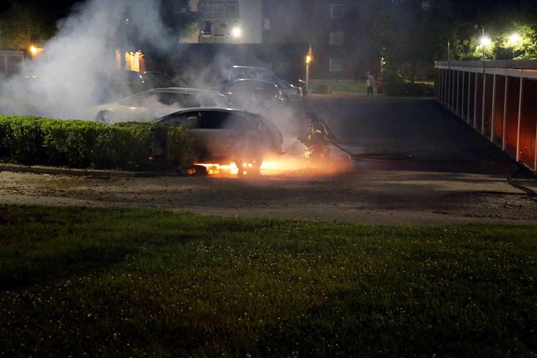 Oroligheterna i Uppsala fortsatte under söndagskvällen. Här brinner en bil på Bandstolsvägen. Polisen i området bär kravallutrustning - sköldar och hjälmar.