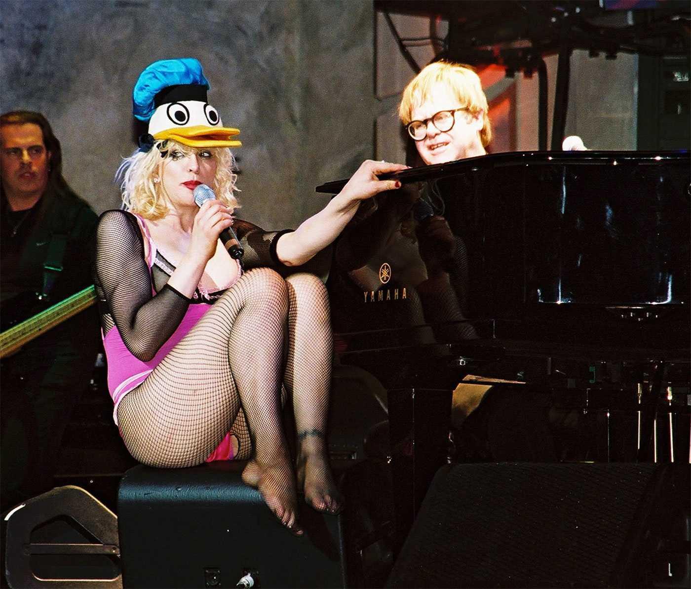 Courtney Love, här på scen tillsammans med Elton John, måste lära sig att hålla näbben. Hennes prat om Hole-återförening kan äventyra hela kalaset.