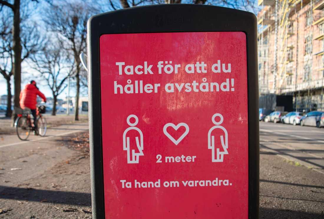 En skylt på en soptunna på Strandvägen i centrala Stockholm uppmanar människor att hålla avstånd. Arkivbild.