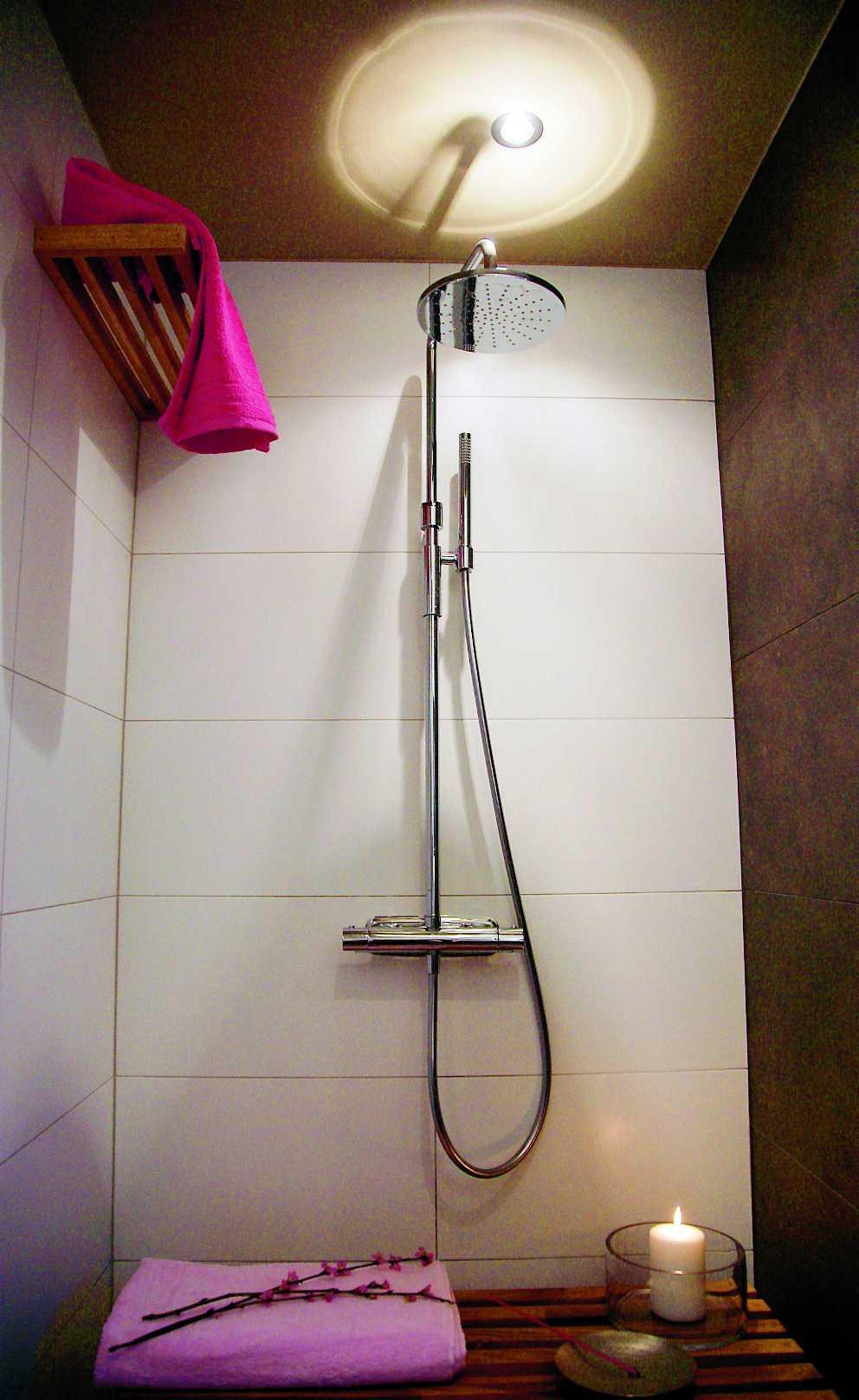 Den separata duschen är smart avgränsad av en enkel vägg. En spotlight speglar sig i duschens metalliska yta och ger en läcker effekt i taket. Träbänken fungerar både som avställningsyta och sittplats.
