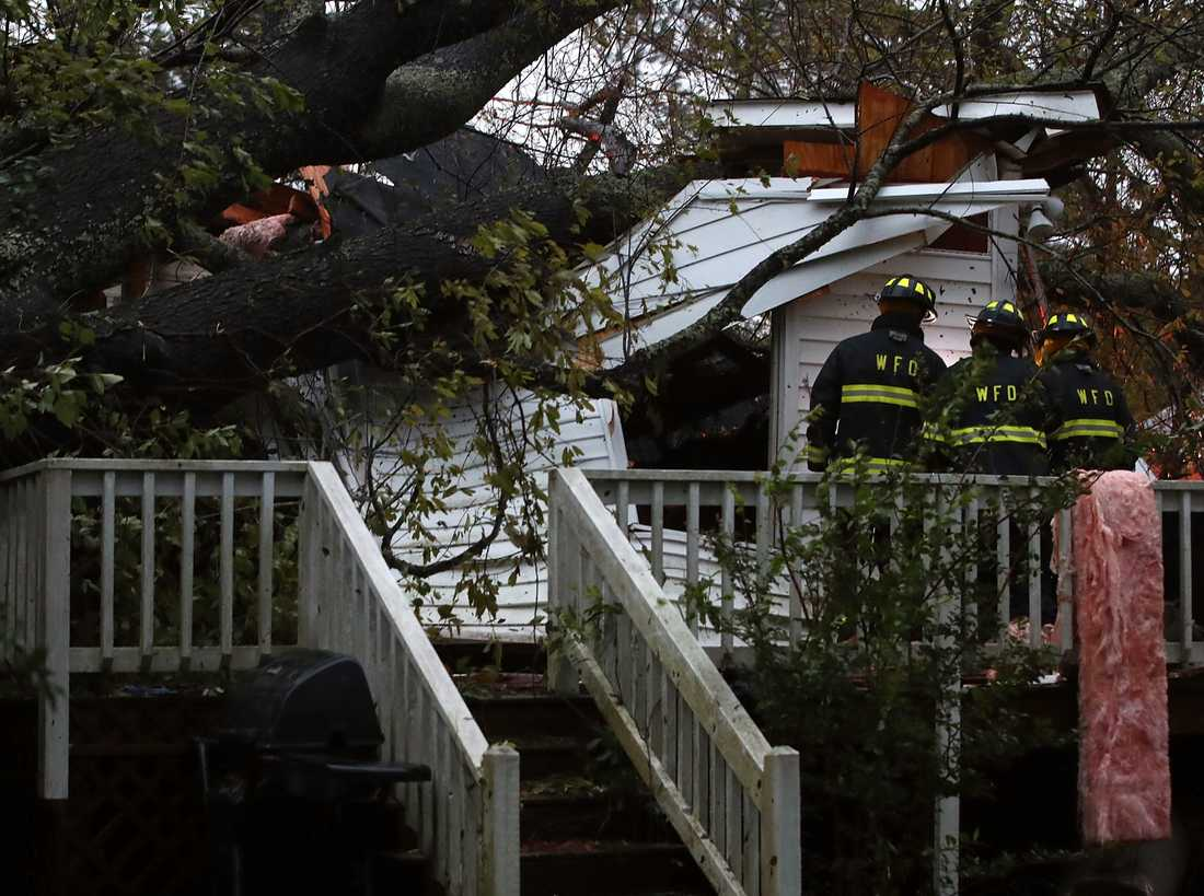 Räddningspersonal utanför ett hem. Ett träd har fallit på huset och tre personer blev instängda.