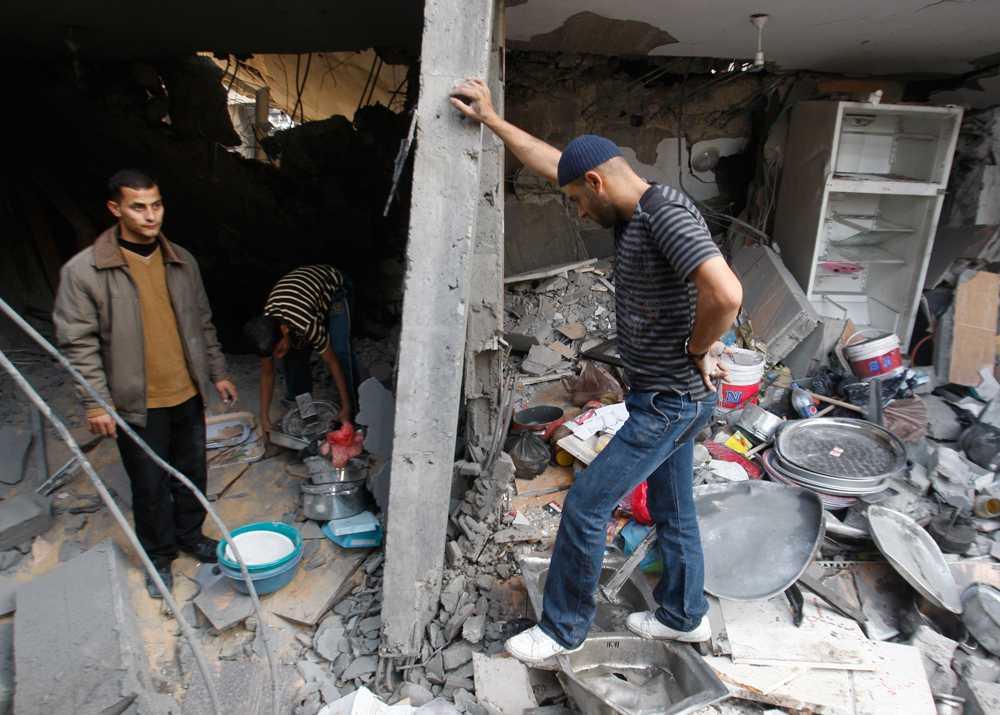 Palestinier letar igenom bråte efter att ett bostadshus bombats.