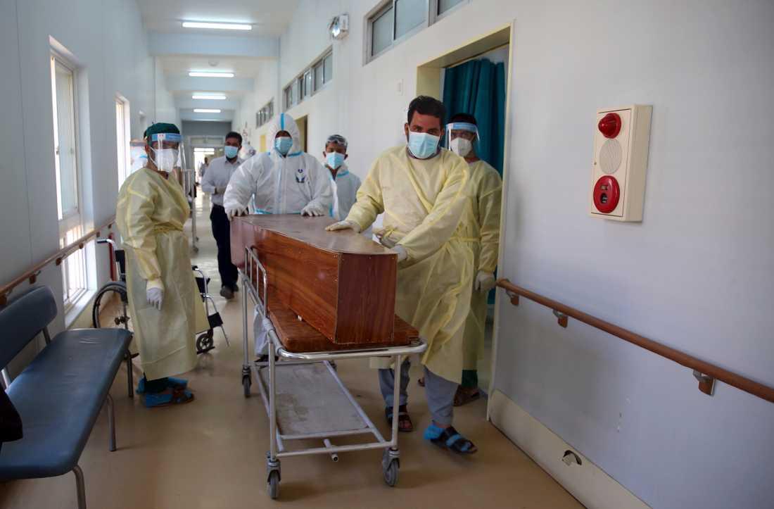 Afghanska vårdarbetare för en man som avlidit i covid-19 längs en sjukhuskorridor i Kabul. Arkivbild.