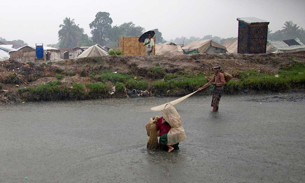 En man bär ett barn i ett läger i Burma.