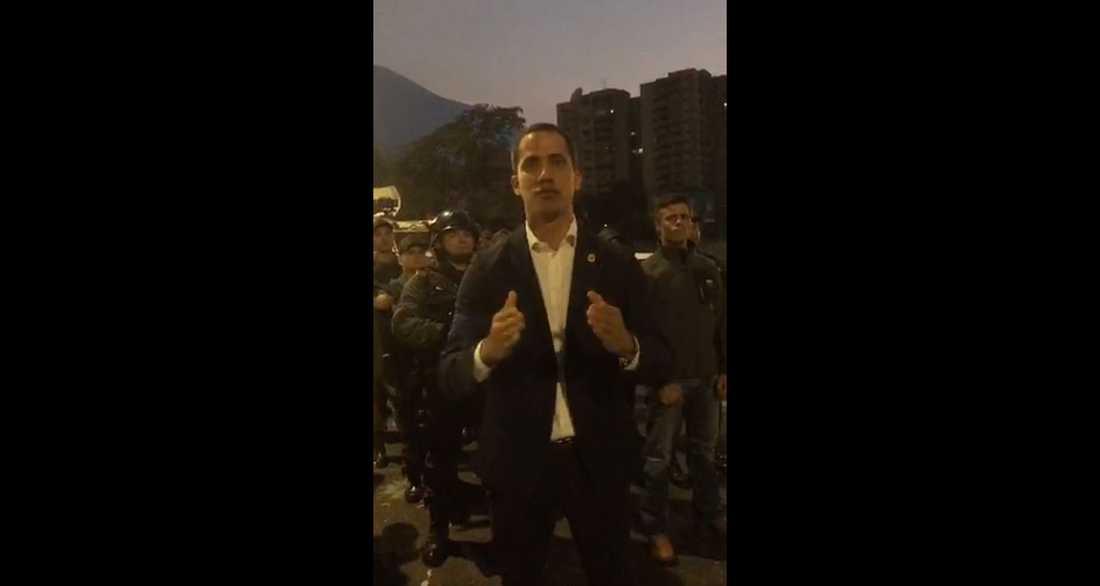 Skärmbild från videon där Juan Guaidó talar och flera militärer står bakom honom.