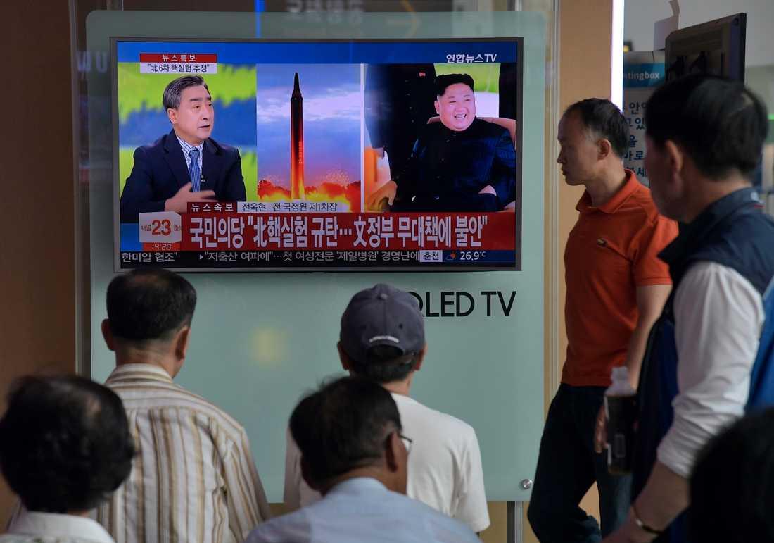 Människor följer nyhetsrapporteringen på en tågstatioön i Sydkorea.