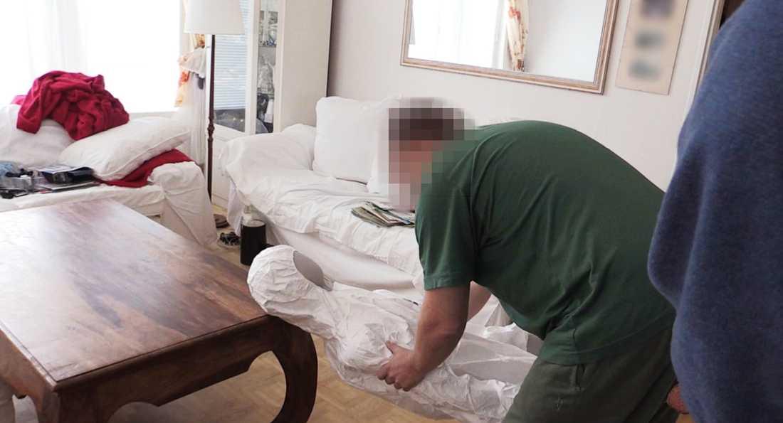 Mannen visar under polisens rekonstruktion hur han hävdar att hustrun dött.