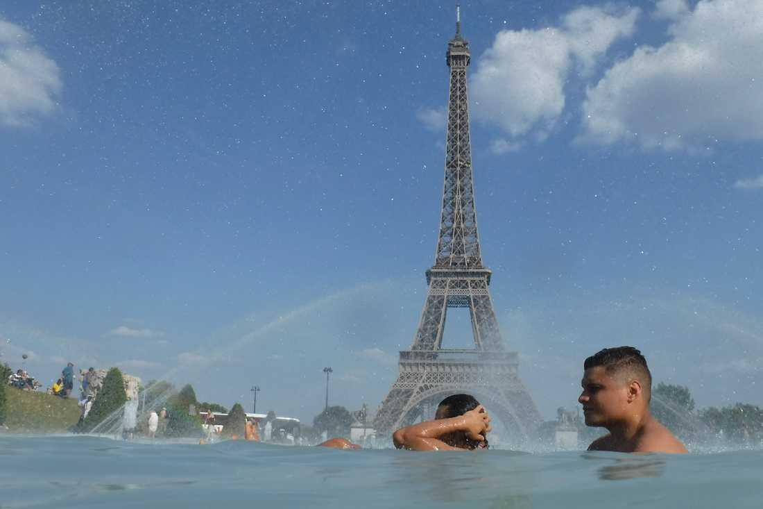 Människor svalkar sig i fontänen på torget Trocadero i Paris på tisdagen.