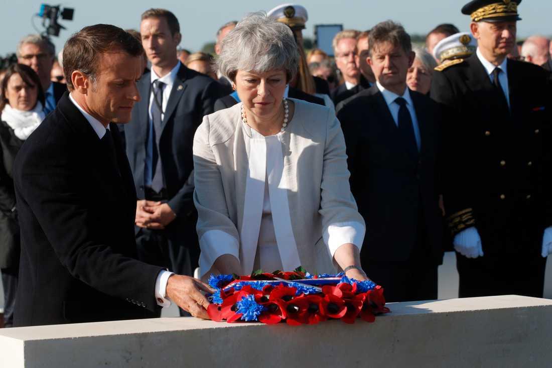 Storbritanniens premiärminister Theresa May och Frankrikes president Emmanuel Macron lägger en krans vid minnesceremonin för de brittiska stupade under D-dagen.