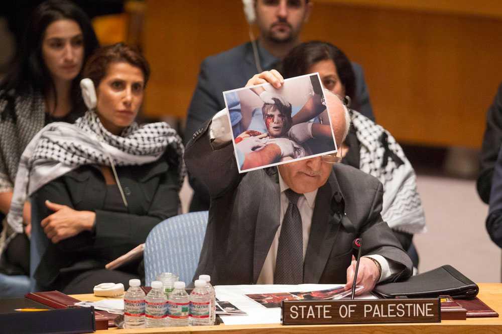 """Den amerikansk-palestinske diplomaten, Riyad H. Mansour, håller under ett FN-möte upp foton på offer och anhöriga och läser upp namn på barn som har mist livet i konflikten. """"Vi är inte statistik, vi är människor"""", säger han enligt Al Jazeera. Mansour uppmanar FN:s säkerhetsråd att sätta stopp för våldsamheterna."""