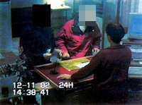 PÅ BANKEN Bilden från övervakningskameran visar hur kidnapparen till vänster tvingar sitt offer att ta ut pengar från kontot.