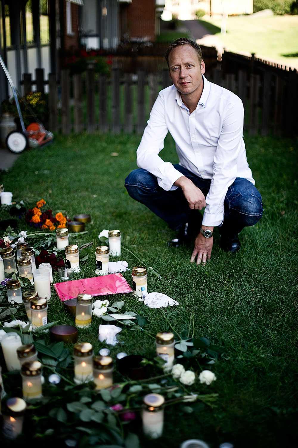 Jens bror Mikael Myringby vid minnesblommor och ljus.