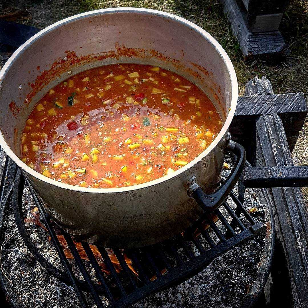 Kyckling- och tomatsoppa över eld.